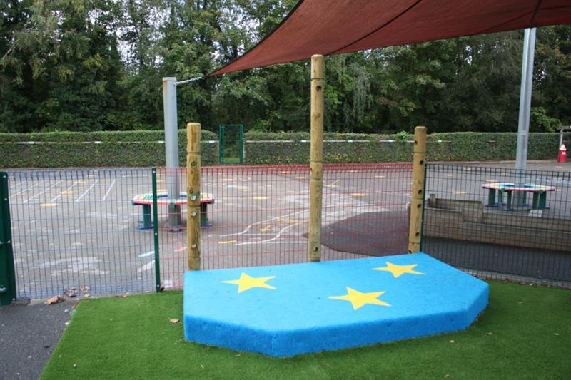A blue performance stage with yellow stars and 3 den making posts at the back of it installed onto artificial grass