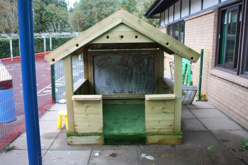 A small playhouse with whiteboard and artificial grass base