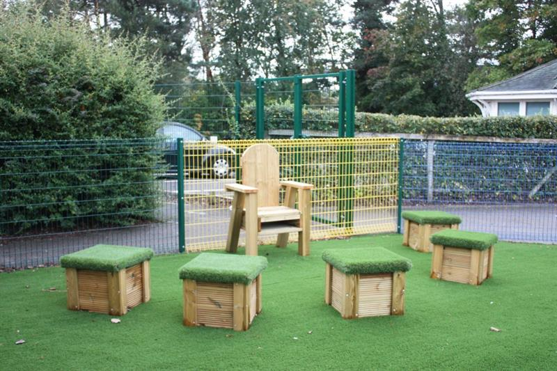 a freestanding storytelling chair surrounded by 5 artificial grass topped seats