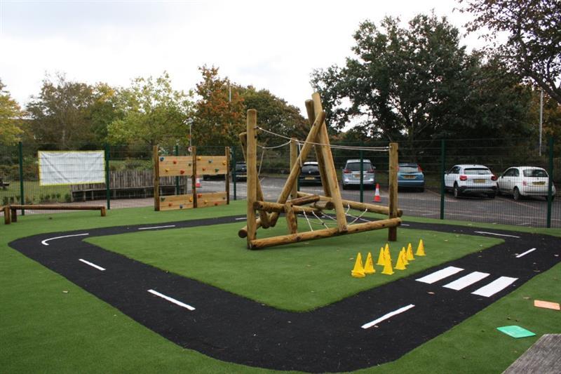 Artificial grass surfacing installed around a black saferturf playground roadway
