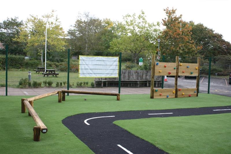 Trim trail equipment installed alongside a playground roadway
