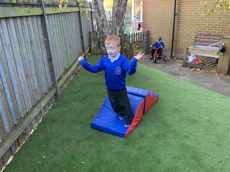 Child jumping off a foam block onto artificial grass