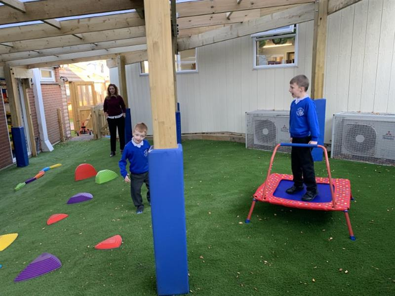 Children playing on artificial grass under a timber canopy