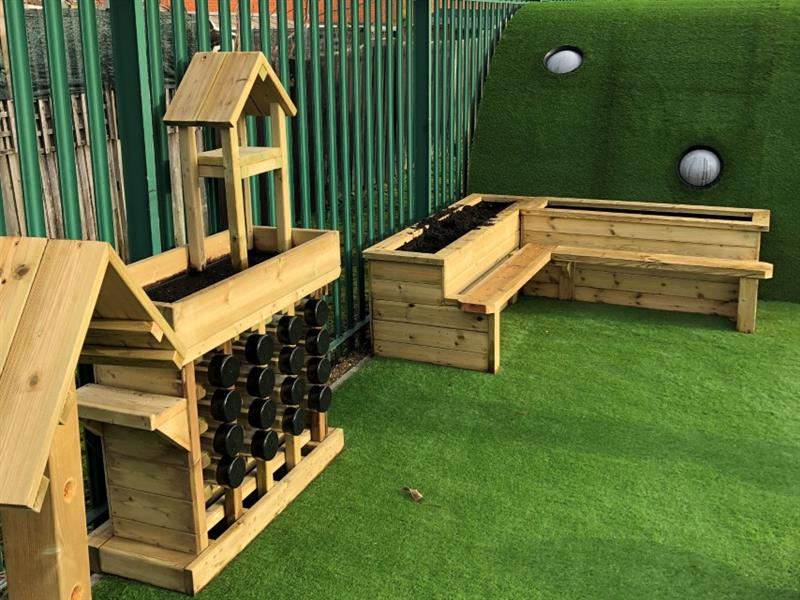 A Bug Hotel and Corner Planter Bench installed in a school Playground