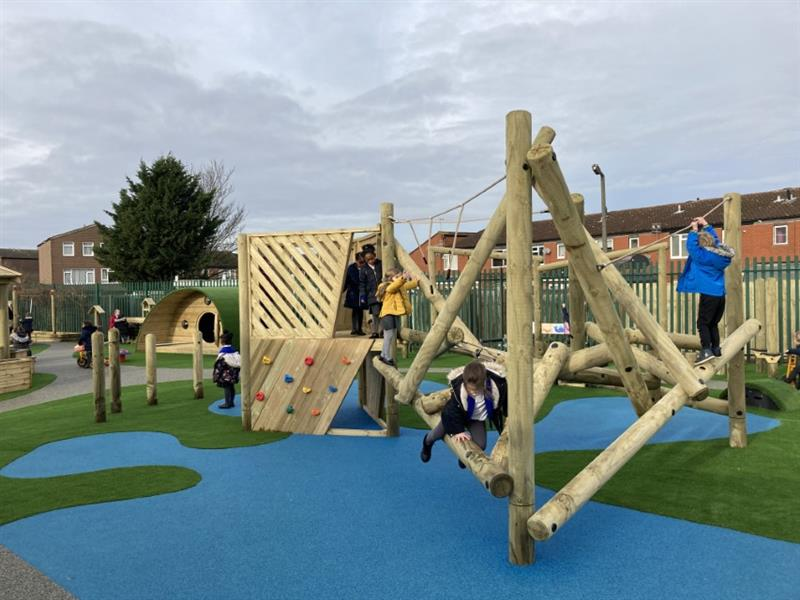 Children swinging and climbing on a rope and log climbing frame