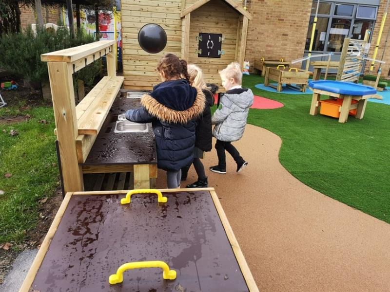 Children baking mud pies in a playground mud kitchen