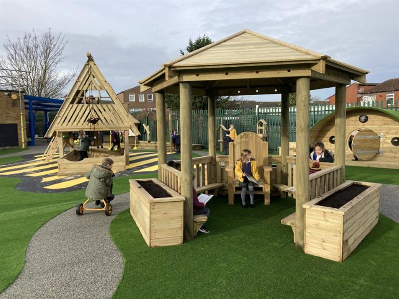 Children sat in a small timber gazebo reading stories