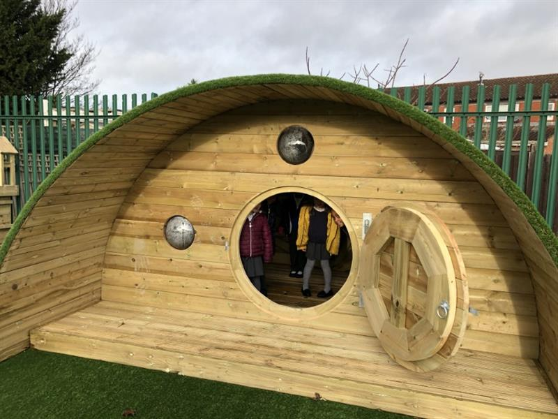 Children playing in a Hobbit House on the playground