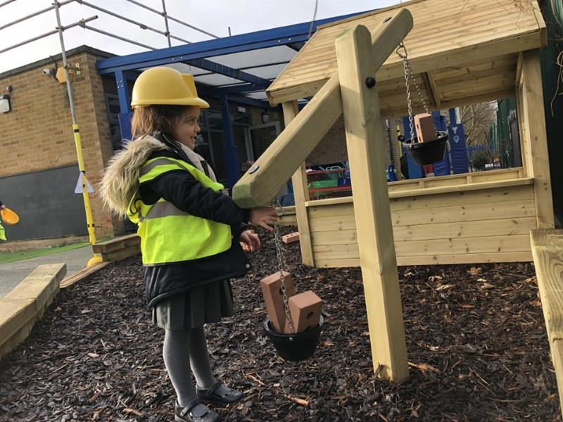 Child weighing play bricks out on a set of playground weighing scales