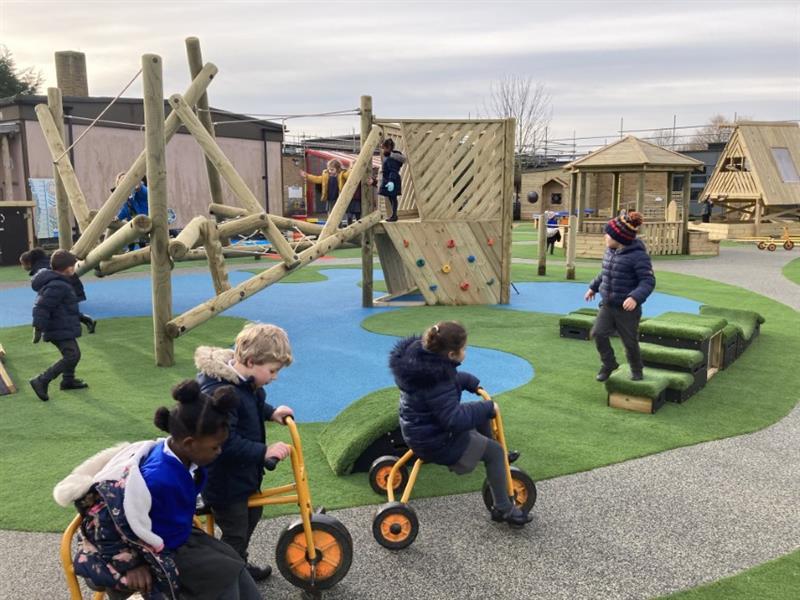 Children riding trikes around a wetpour pathway in the school playground