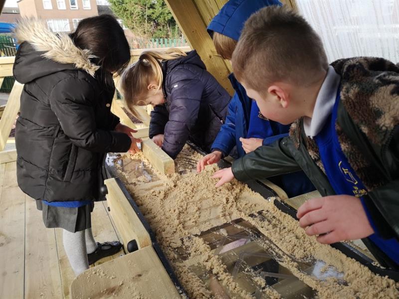 Children moving sand along a conveyor belt in an investigative playhouse