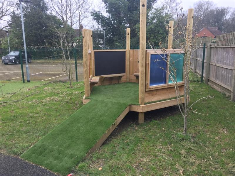 Imagination station installed onto grass with artificial grass placed inside of the station, there are also two pannels, one green and one blue with a chalkboard inside. Behind the play area is the staff car park with one black car parked inside of it.
