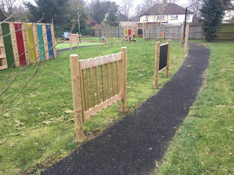 Different panels along the pathway including a giant chalkboard. The panels have been installed onto the grass with the eight-metre sensory tunnel, sensory spinners and imagination station in the background.