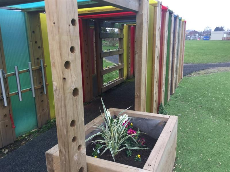 Close up photo of a large planter at the end of the sensory tunnel which has been installed on top of a pathway in the middle of the school field. There are pink, white and yellow flowers inside of the planter.
