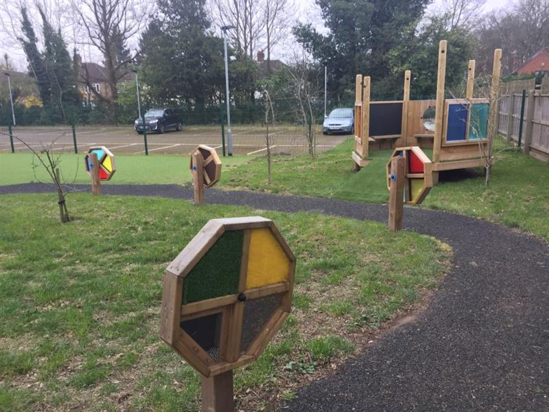4 sensory spinners have been installed along the pathway onto grass in front of the imagination station which has also been installed onto grass. Behind the play area is the staff car park where a blue car and a black car are parked.