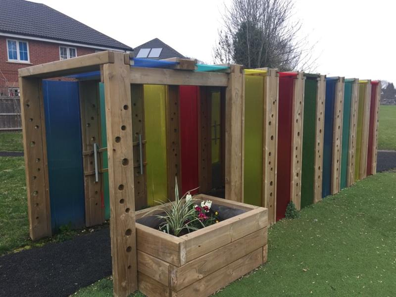 Eight-metre sensory tunnel with yellow, red, green and blue polycarbonate panels. A large planter has been installed at the end of the tunnel for children to plant flowers and plants in.