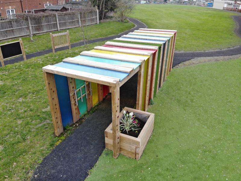 An eight-metre long sensory tunnel with blue, green, yellow, and red polycarbonate panels with a planter installed at the end of the tunnel. There are musical panels installed at the side of the tunnel.