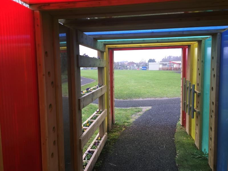 Photo was taken inside of the sensory tunnel with red, yellow, green and blue panels, musical equipment and long planters with yellow and purple flowers in. You can see the school building through the tunnel.