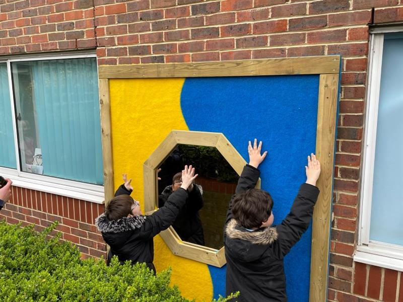 2 children wearing black coats are playing with the large sensory panel featuring blue and yellow safe turf with a mirror in the middle. One child is touching the blue safe turf and one child is touching the mirror and looking at his reflection.