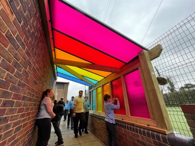 One child stood underneath the timber canopy banging on the red polycarbonate panel whilst 2 more children walk through the tunnel and 3 teachers supervise. There are pink, red, orange, yellow, green and blue polycarbonate panels on the timber canopy.