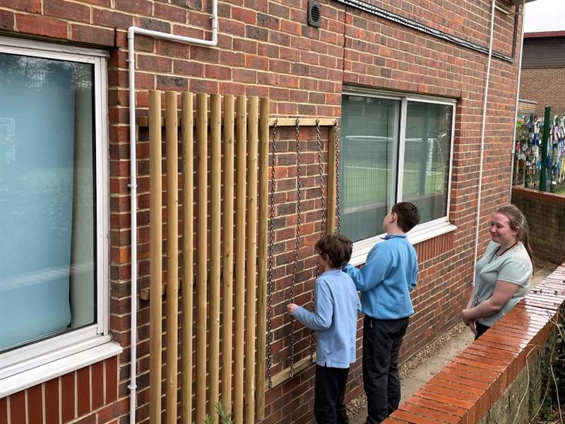 2 children wearing light blue long sleeve tops are playing with the dowels and chain which has been installed onto the side of the school building on the wall, whilst one teacher wearing a green top stands with the children smiling.