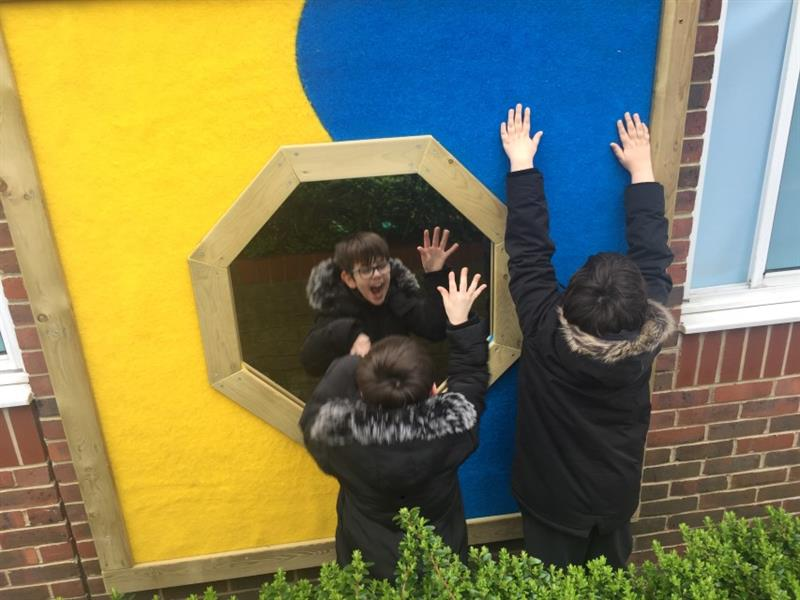 2 children wearing black coats playing with the sensory wall panel which includes yellow and blue safe turf and a mirror in the middle. It has been attached to the school building next to the window.
