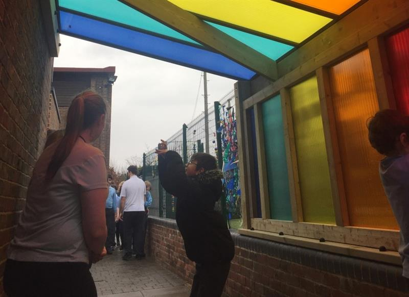 2 children playing underneath the bespoke timber canopy with multicoloured polycarbonate panels whilst one teacher stands near the brick wall.