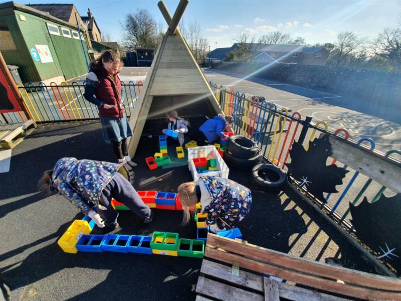 2 children stood playing outside of a wigwam den and 2 children playing inside of a wigwam den, building structures with plastic blocks with a teacher.