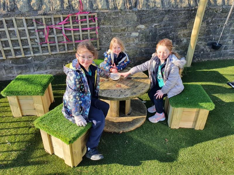 3 reception children girls sat on small artificial grass topped seats at a circle wooden table socialising.