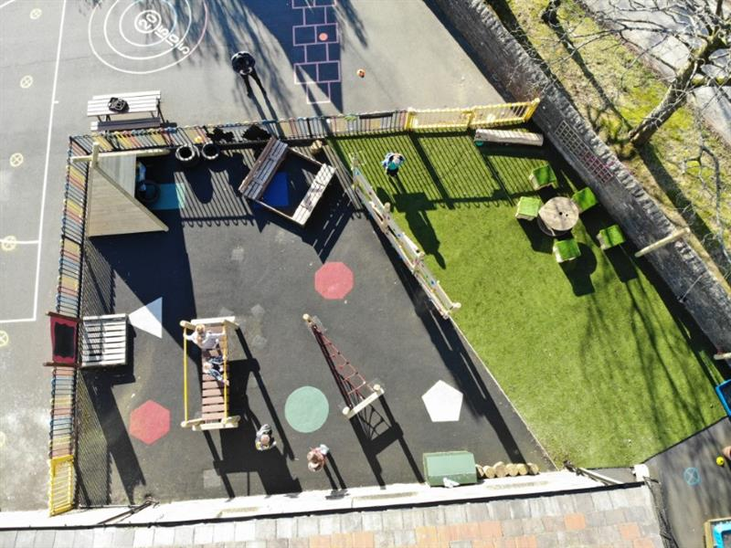 Airel view of children exploring their new playground which includes a trim trail, wigwam den, wetpour surfacing and an artificial grass area.