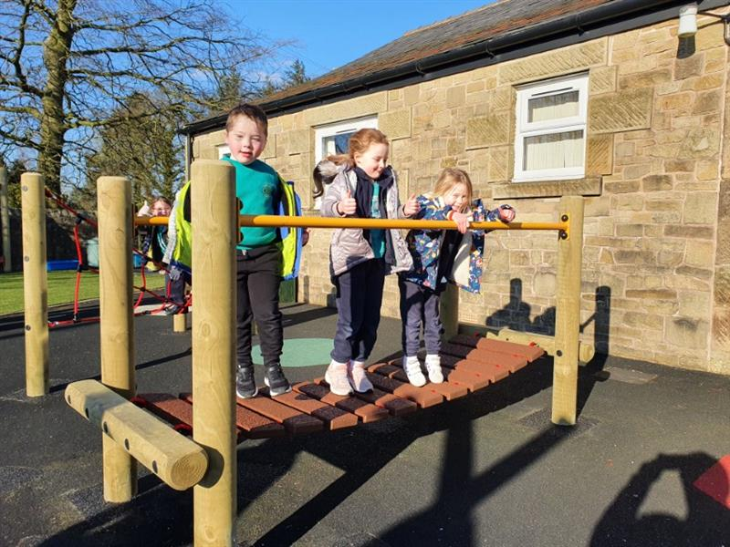 Three children jumping up and down on a Clatter Bridge installed onto black wetpour surfacing