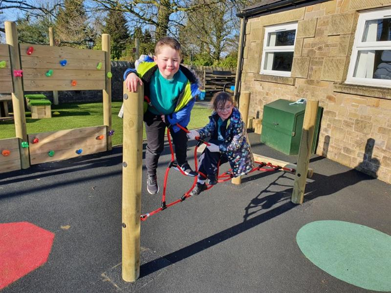 2 reception children wearing coats playing on a twist net with red ropes and timber beams