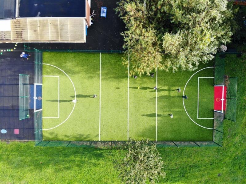 Children playing football on a MUGA Pitch - ariel photo from above