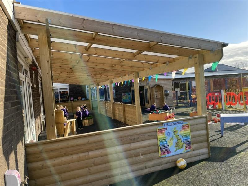 A timber canopy with cladded sides installed onto a school playground
