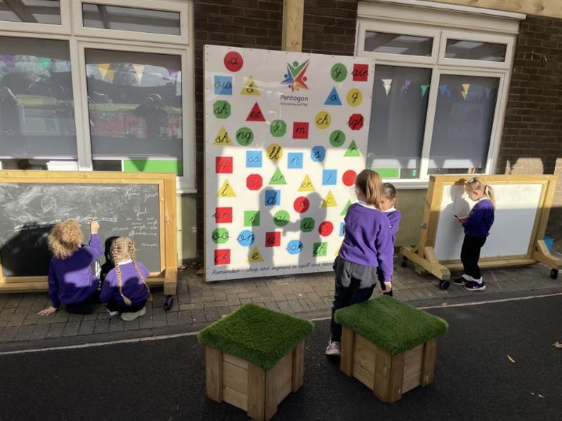 KS1 children playing phonics games outdoors