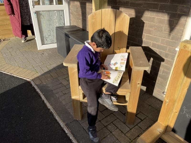 Child reading a story sat in a freestanding storytelling chair