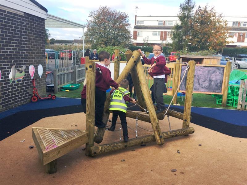 Nursery children climbing on an introductory climbing frame