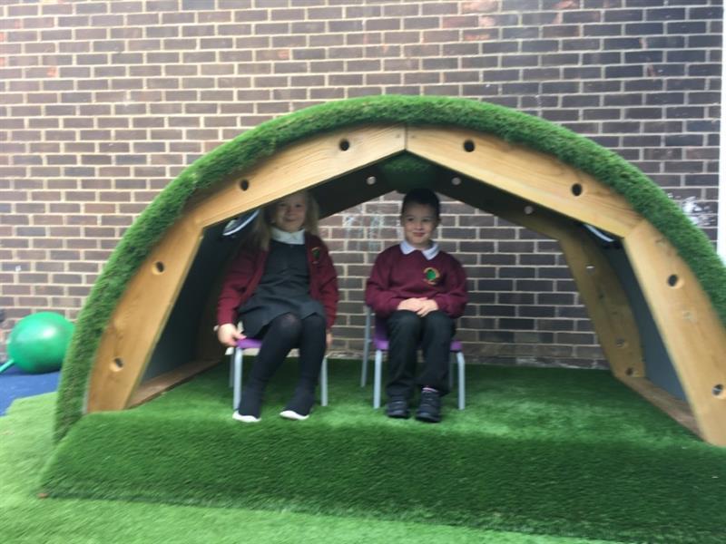 Nursery children sat in a playground den