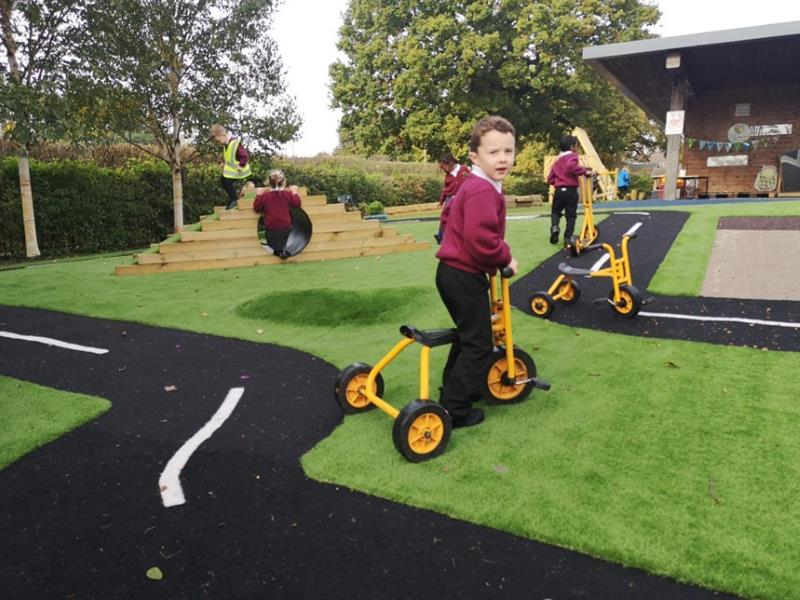 Children riding trikes around a saferturf roadway