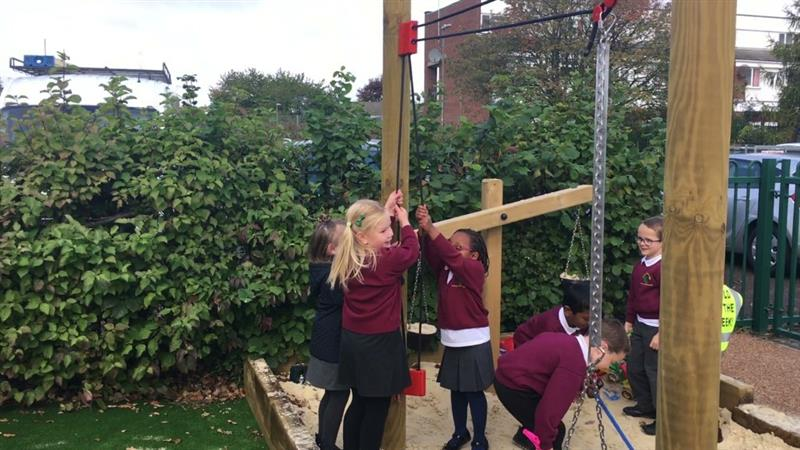 Children working together to use a rope and pulley materials mover