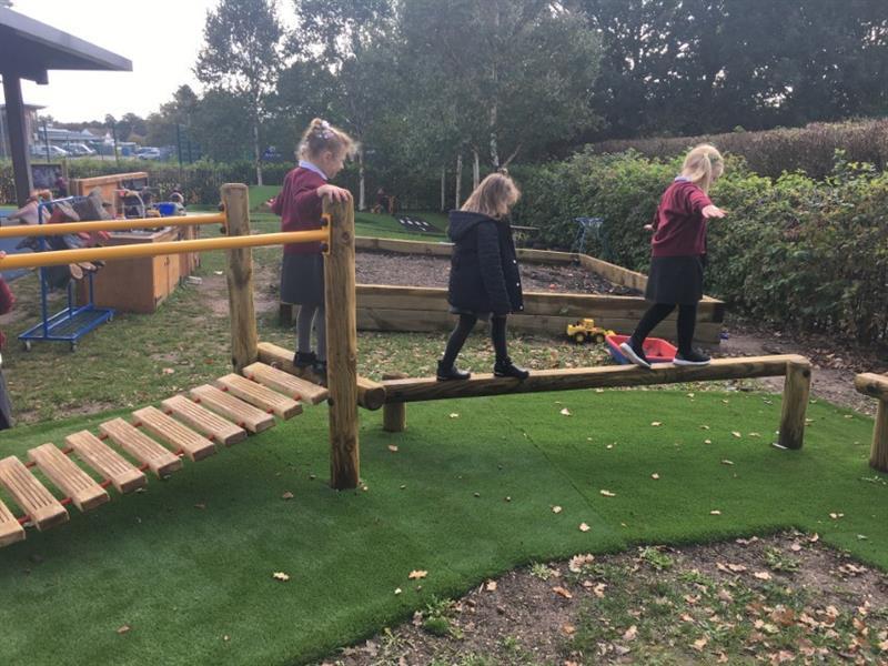 Early years children walking across trim trail equipment