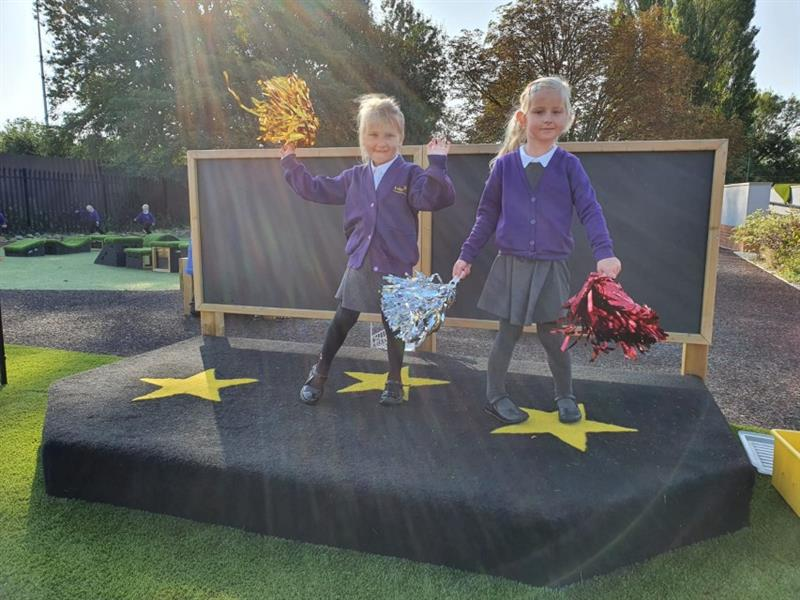 Children performing on a performance stage on the playground