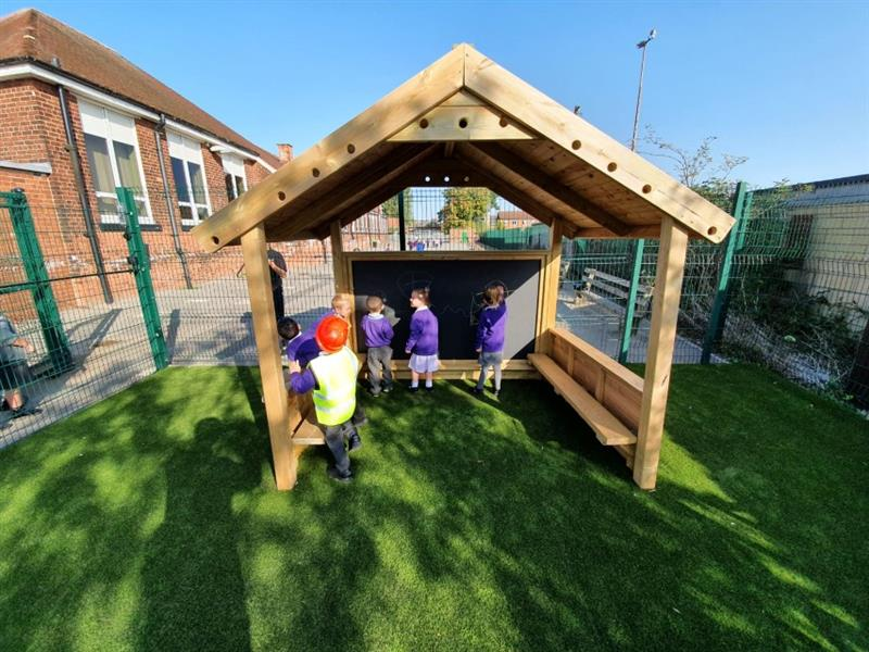 EYFS children role playing in a playhouse on artificial grass