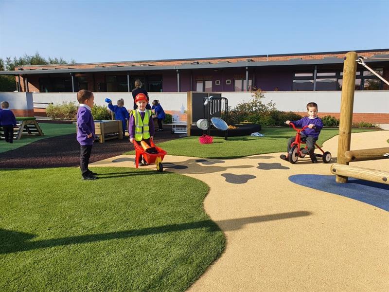 Happy children riding bikes on school playground surfacing. One child has a wheel barrow in hand.