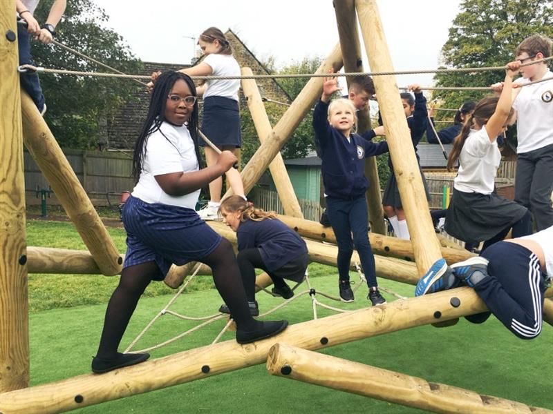 Children balancing on beams on a playground climbing frame