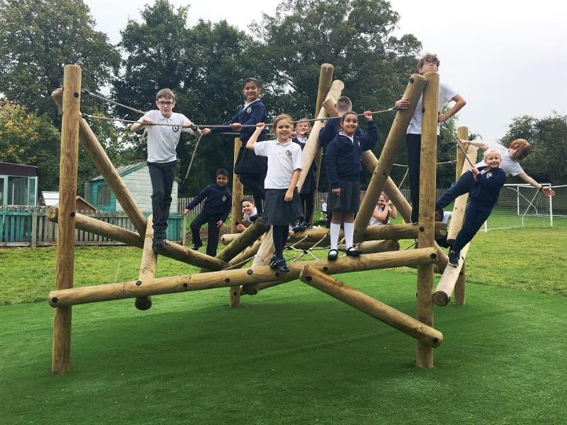 Children climbing on a log and rope wooden climbing frame