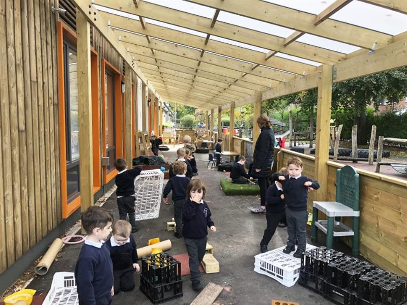 Children participating in free flow outdoor learning activities under a timber canopy