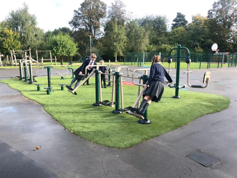 Children using outdoor gym equipment that has been installed on top of artificial grass on the school playground