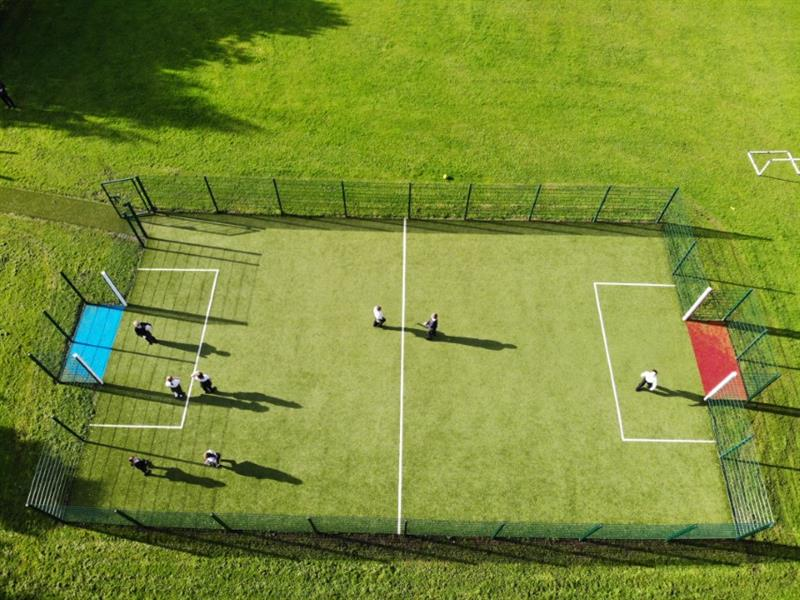 A muga with children playing football on it installed onto a school field