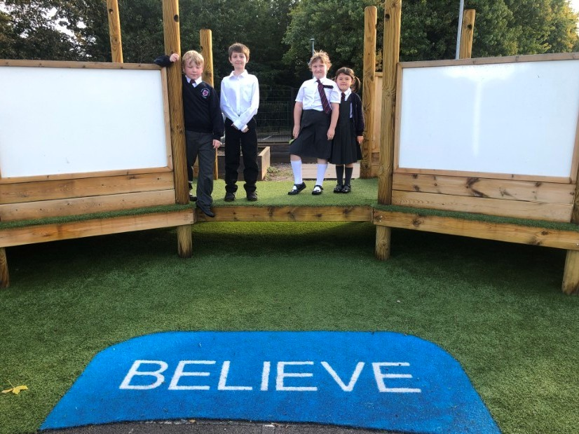 Children standing on imaginative and creative school playground equipment that has been installed onto artificial grass surfacing